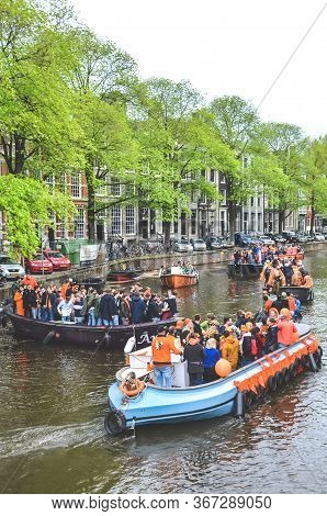 Amsterdam, Netherlands - April 27, 2019: Party Boats With People Dressed In National Orange Color Wh