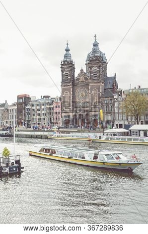 Amsterdam, Netherlands - April 27, 2019: Canal In The Center Of The Dutch Capital. Boat On The Canal