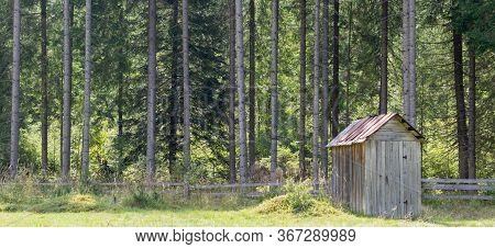 Shed In The Woods. Fenced Rural Property With Old Wooden Shed.