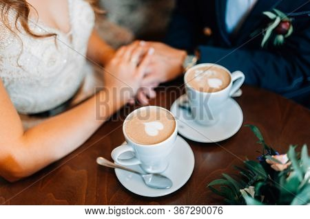 Bride And Groom Holding Hands Together. Romantic Moment. Coffe Cups With Hearts