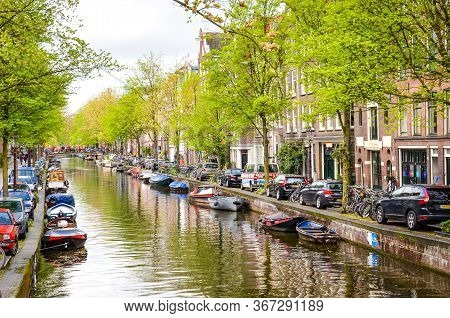 Amsterdam, Netherlands - April 27, 2019: Small Boat On The Canal In The City Center Of The Dutch Cap