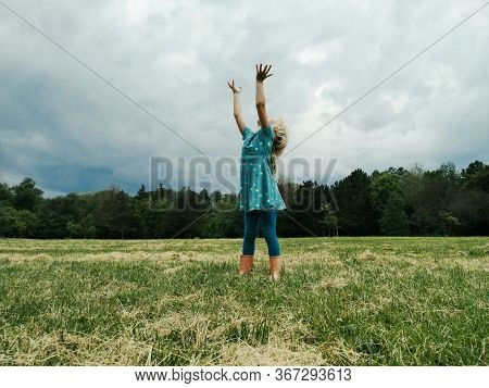 Little Girl Child Stand On Meadow With Hands Up To Sky In Hope. Freedom, Innocence And Adolescense C