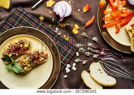 Open Toasts With Different Toppings On A Black Background. Assortment Of Italian Traditional Brusche