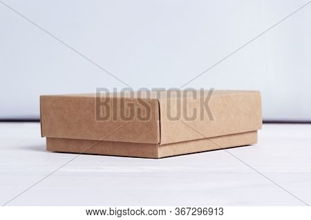 Cardboard Box. Package Isolated On White Wood Background. Craft Paper Box Side View. Small Square Cl