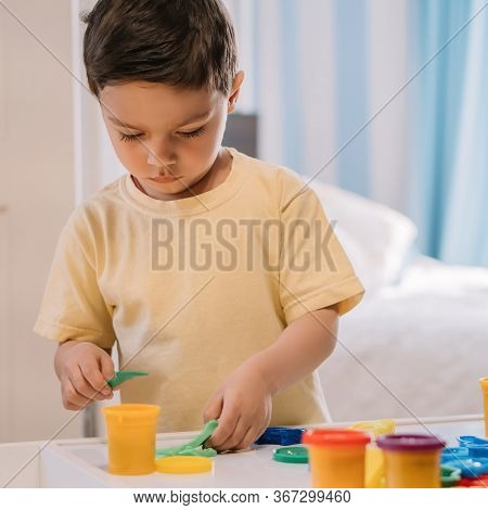 Cute, Concentrated Kid Holding Spatula While Sculpting With Plasticine Near Molds And Containers