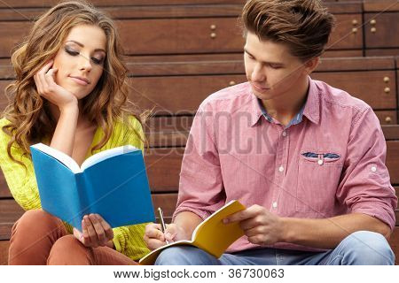 couple of students with  sitting at campus park and reading book.