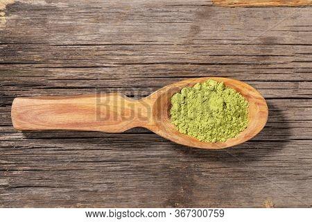 Wooden Spoon With Japanese Green Matcha Tea Powder On Old Wooden Board. Matcha Tea Is Organic Health