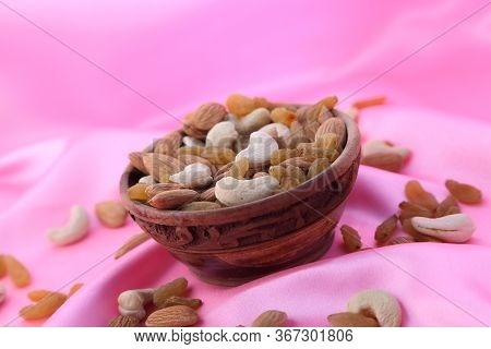 Delicious And Healthy Mixed Dried Fruit, Nuts And Seeds In A Wooden Bowl On Pink Silky Background.