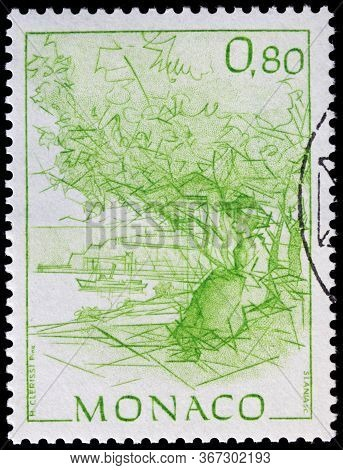 Luga, Russia - April 10, 2020: A Stamp Printed By Monaco Shows Woman Sitting Under Olive Tree, Circa