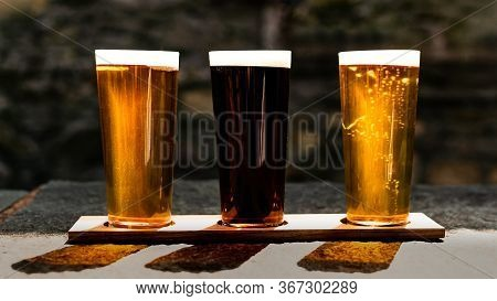 Three Craft Ales Lined Up In The Sunshine At Beer Garden In Cartmel, Cumbria, Uk