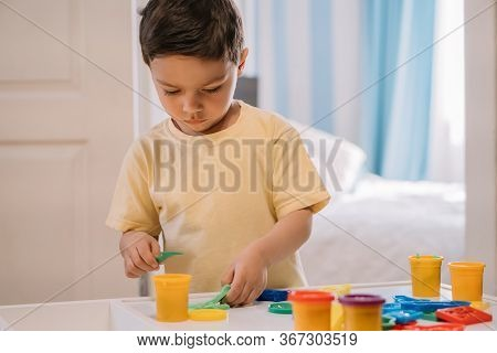 Cute, Attentive Boy Holding Stick While Sculpting With Colorful Plasticine