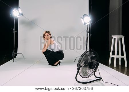 Side View Of Attractive Model Looking At Camera Near Floodlights And Electric Fan In Photo Studio
