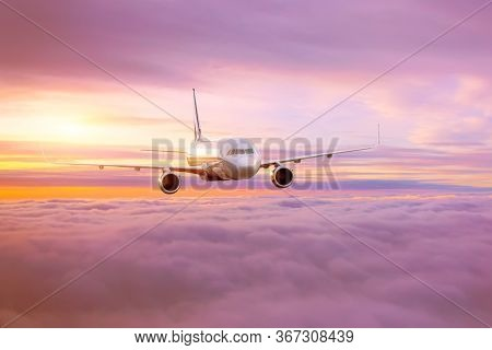 Passenger Airplane In The Morning Sun Flies High Above The Pink-tinted Clouds With Glare On The Fuse