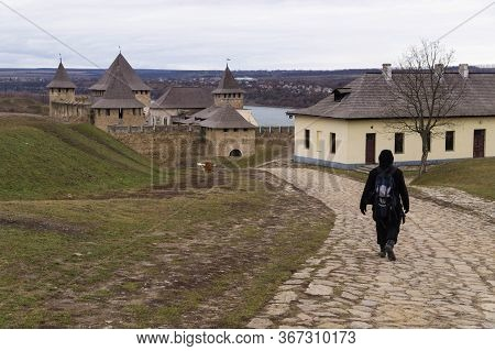 Male Tourist With A Backpack Goes Along A Cobblestone Road Towards Khotyn Fortress