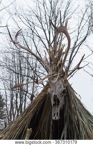 A Deer Skull Mounted On Top Of A Reed Hut - Dwelling Of Ancient People Of The Neolithic Era