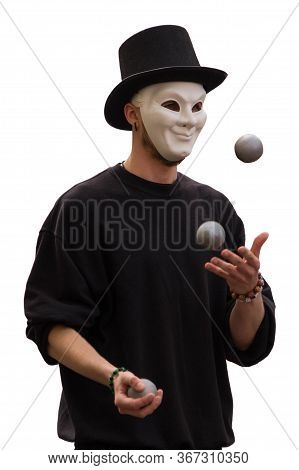 Juggler In A White Mask And A Black Hat Juggles With Gray Balls On A White Background
