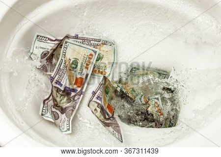Loss Of Money. Bad Investment Or Investment. Cash Dollars Are Flushed Into The Toilet
