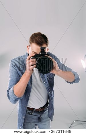 Photographer Taking Picture With Digital Camera Near Floodlight In Photo Studio