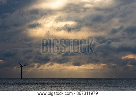 Dark Dramatic Sky Over Sea Horizon Landscape With Wind Turbine Silhouette. Skyscape Background Image