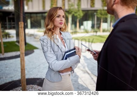 young caucasian businesswoman looking interested to her interlocutor outdoor in front of business building. outdoor, unofficial, meeting, sharing information, selling, making deal
