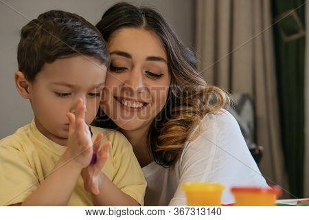Happy Woman Hugging Adorable Son Sculpting Plasticine Figures
