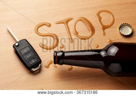Drunk Driving. Beer Bottle And Spilled Beer In The Shape Of The Word Stop. Car Keys