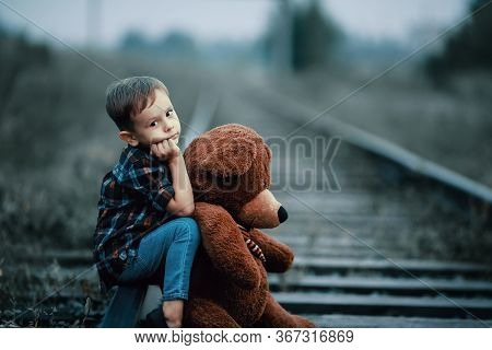 An Abandoned Homeless Child, An Orphan. A Lonely Boy Hugs A Stuffed Toy And Sits On The Tracks, Look