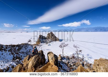 Lake Baikal, Russia - March 11, 2020: Girl Looks To Cape Burhan On Shamanka Rock In Olkhon Island In