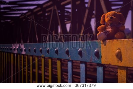 A Small Cuddly Toy Was Sitting On The Colorful Rail Of An Old Bridge