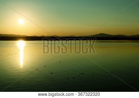 Sea sunset landscape, sea nature. Sea water surface lit by sunset light. Summer sunny water scene in picturesque tones. Sea summer nature with mountains at the horizon - panoramic sea water view