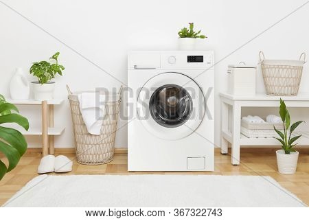 Interior Of Cosy Laundry Room With Washing Machine And Carpet