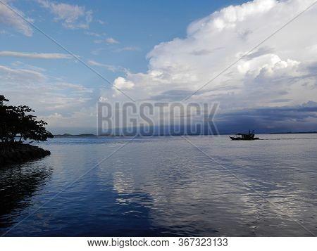 Boat On Tranquil Kinabatangan River With Reflections , Sabah, Malasia