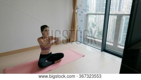 Woman watch tv and do yoga at home