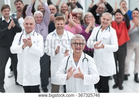 Group doctors and patients clapping their hands to celebrate recovery