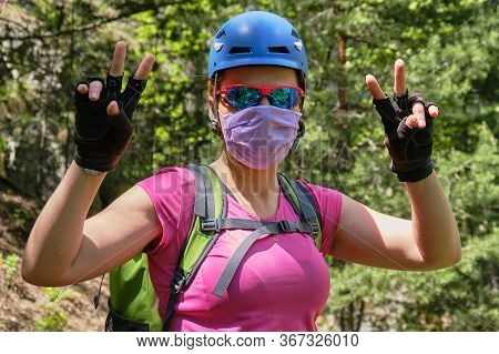Woman Alpinist Wearing A Medical Mask And Helmet, Shows A Victory Sign With Both Hands. Concept Of C