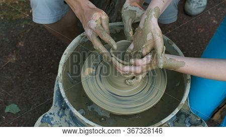 The Master Potter Teaches The Child To Make A Clay Jug On A Modern Potters Wheel With An Electric Dr