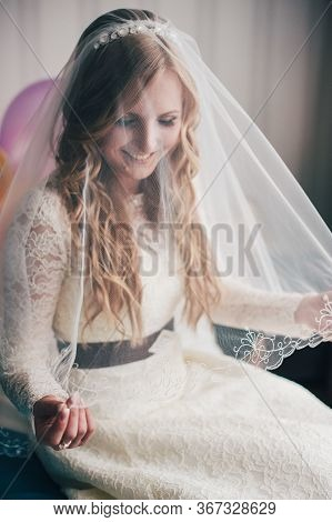 Beautiful Happy Smile Young Girl Bride. Gently Looking Straight Through The Veil. Hands Holding A Ve