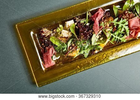 Salad with lettuce and jamon. Fancy meat and vegetables mix served on transparent yellow plate. Luxury side dish on dark table top view. Delicious restaurant course serving overhead shot