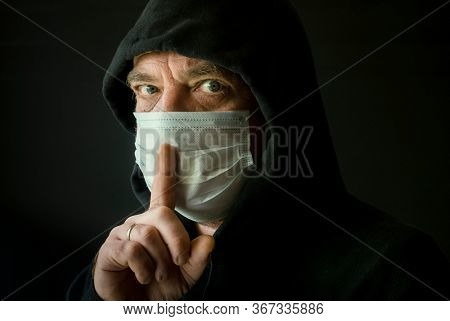 A man in a black hoodie and a medical mask with a finger on his lips. Coronavirus conspiracy and fake news concept