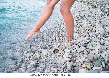 A Girl With Bare Feet Is Walking Along A Rocky Beach. A Girl At The Sea.woman Bare Foot Walking On T