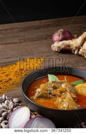 Chicken Massaman Curry In Black Bowl With Herb And Spices On Wooden Background. Thai Authentic Food
