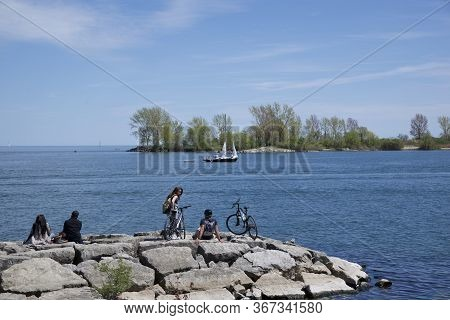 Toronto, Ontario / Canada - May 21, 2018: Group Of People Resting On The Rock In Lake Ontario