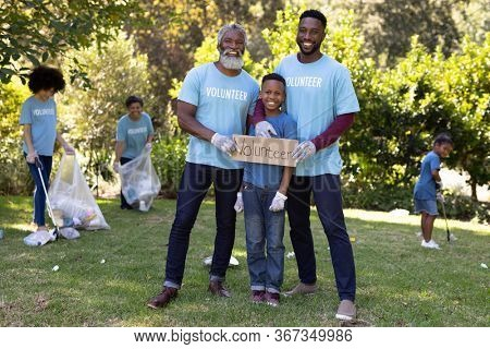 Mixed race boy spending time outside with his family, holding a volunteer sign with his father and grandfather, looking at the camera and smiling, all wearing blue volunteer t shirts, on a sunny day