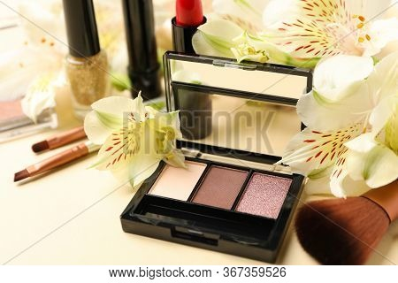 Different Makeup Cosmetics And Flowers On Beige Background. Female Accessories