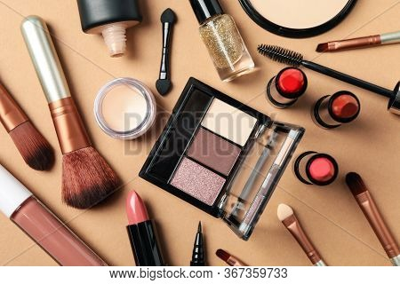 Different Makeup Cosmetics On Brown Background. Female Accessories