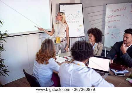 Businesswoman holding a presentation. Businesswoman pointing at the projector screen. Office meeting environment.