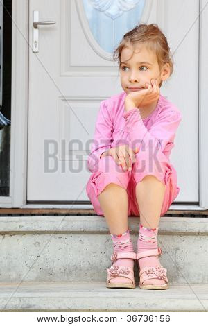 Little girl sits on stairs near white door, smiles frigidly and looks away.