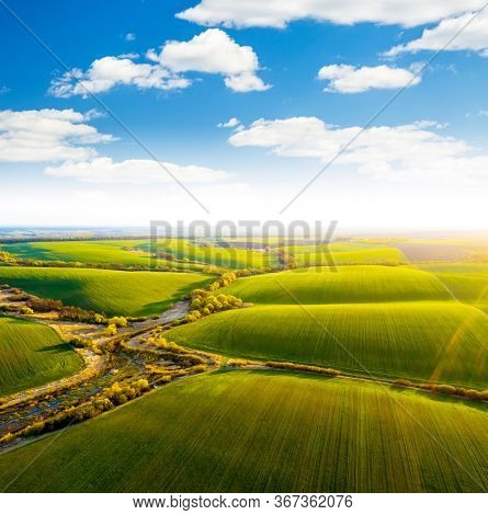 Abstraction agricultural area, green wavy fields in sunny day. Aerial photography, top view drone shot. Location place of Ukrainian agrarian region, Europe. Photo of ecology concept. Beauty of earth.