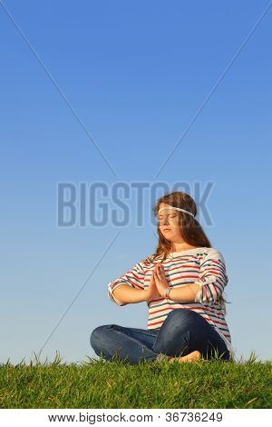 Fat girl meditates and thinks at green grass at background of blue sky.
