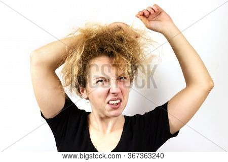 Close-up Of A Sad Girl With Disheveled Yellow Dyed Hair Pulling Her Hair And Grimacing. On White Bac